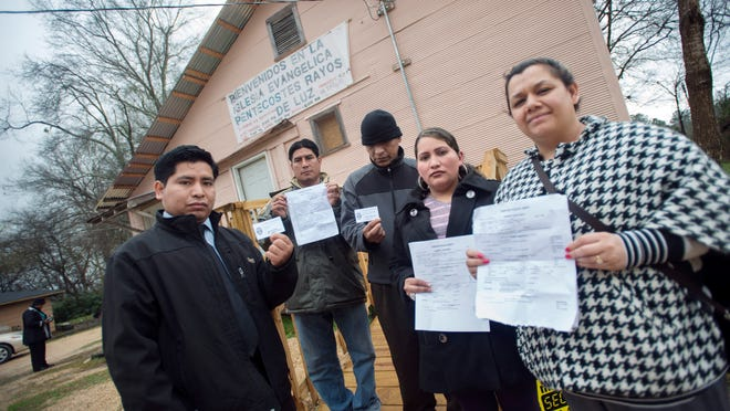 Canton residents, from left, Esbin Orozco, Arvin Sanchez Lopez, Victor Perez, Sara Hernandez and Yesenia Leveron, display crime reports and case cards they're received after reporting crimes against them recently. They and other members of Canton's Latino community feel that they are regularly targets of violence and crime and fear that the situation could escalate into a race war .