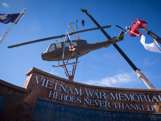 A Vietnam War-era Huey helicopter is put into place at the new Vietnam War Memorial at Veterans Memorial Park on Tuesday morning. A re-dedication ceremony for the monument, to formally unveil the Huey, is scheduled to take place on March 26th.