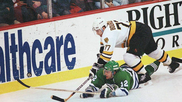 Boston Bruins defenseman Ray Bourque reaches over the back of Hartford Whaler Dean Evason trying to get to the puck behind Boston's goal during first period action Dec. 13, 1990, in Boston. The NHL hasn't had best-of-five playoff series since 1986. That's changing for this year with the league expanding to 24 playoff teams as part of its restart. Stephan Savoia/AP, file