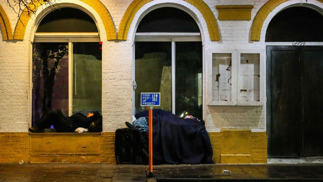 Homeless people sleep on a deserted 6th Street in downtown Austin in March.