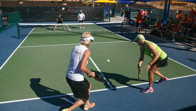 Jane Porphir, looks on as her doubles partner Vicky Noakes, right, returns a volley from their opponents Nancy Schwarz and Barbara Durrant, during Huntsman World Senior Games pickleball action at the Little Valley Pickleball Courts in St. George, Monday, Oct. 12, 2015.