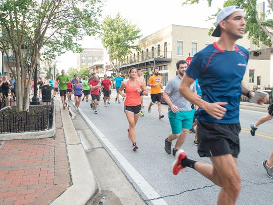 Runner take off down Palafox Street during the weekly World of Beer Running Club's run in Pensacola on Wednesday, April 5, 2017.