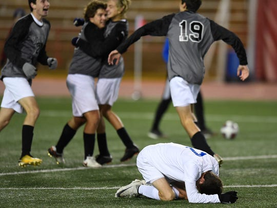 Castle's Joseph Kerney (7) puts his head down on the field as the Harrison Raiders celebrate winning the Class 3A Boys Indiana High School Athletic Association Soccer State  Championship at Michael A. Carroll Stadium in Indianapolis Saturday, October 28, 2017.