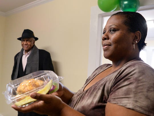Owner Deshawn Reid, right, holds a sandwich plate near