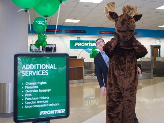 A playful Jonathan Freed, Frontier Airlines director of corporate communications, peeks out from mascot Chocolate Moose during a ceremony celebrating new Frontier Airlines service at Pensacola International Airport on Tuesday, April 24, 2018.