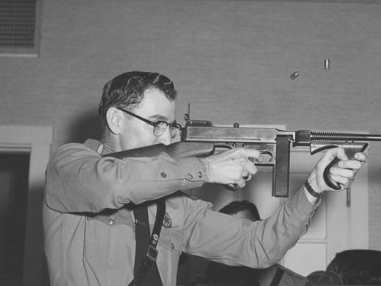Brass casings are suspended in the air as Trooper Bill Cooksey uses a .45 caliber Thompson sub-machine gun during a safety demonstration in Waco around 1959, when he was working as the Safety Education Officer for the Department of Public Safety.