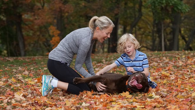 Jenni Brand and her 6 year-old son Jamie play with their chocolate labrador Beau at Rockford Park.