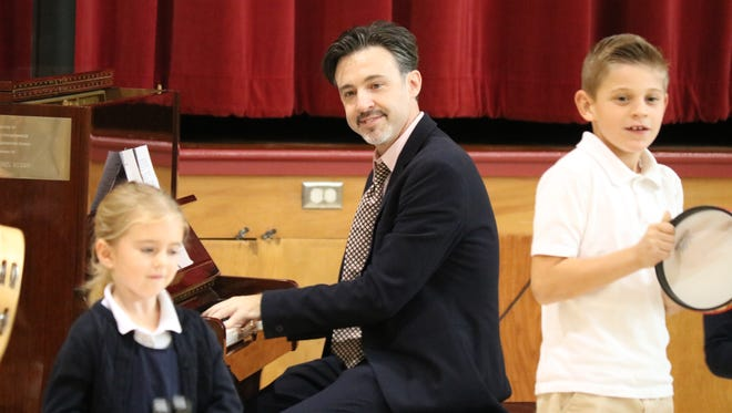 Matthew Ball, The Boogie Woogie Kid, performs for and with students at Immaculate Conception School on Friday.