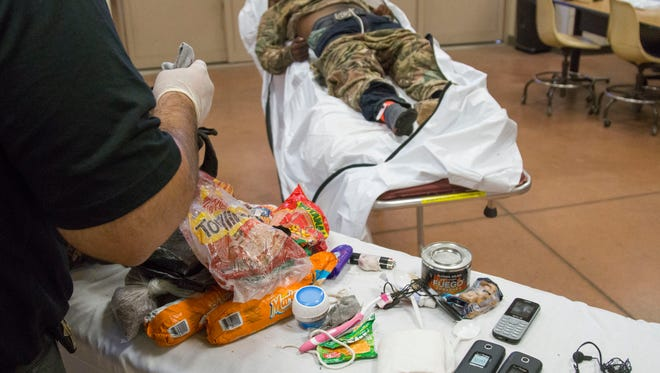 Investigator Trevis Hairston inspects the belongings of a migrant who died in the southern Arizona desert. The Pima County Medical Examiner's Office can use such personal effects to help identify border crossers.