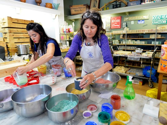 Sunrise Soap Company owner Christina Clarke, center, and assistant Ariel Linebaugh make rainbow-themed soaps at the store in York.