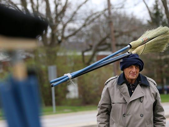 Jim Richter sells brooms Monday at the corner of 71st