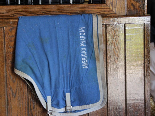 One of American Pharoah's blankets at his stall.