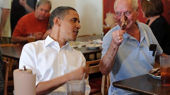 President Barack Obama shares a bite with a customer at 12 Bones.