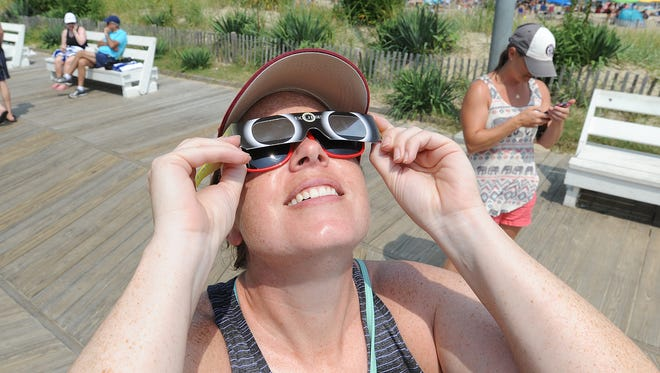Bridget McGeady, of Baltimore, looks through glasses at the solar eclipse that was watched by many on the boardwalk at Rehoboth Beach on Monday, Aug. 21.