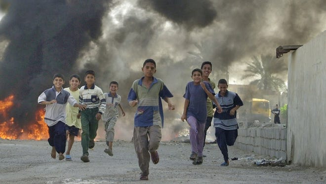 In this May 2004 photo, Iraqi children run from a burning barricade after fighting in the Sadr City area of Baghdad, Iraq. A Wausau Army physician served in Sadr City during this period of the war, which is dramatized in a new miniseries airing on the National Geographic channel.
