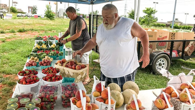 Arlen Johnson sells produce at his Good Ol' Boys Produce stand located on Woodruff Road in the Five Forks area. Johnson moved a few miles down the road after traffic became so congested his customers told him it was getting too hard to pull in and out of the parking lot where he was formerly located.