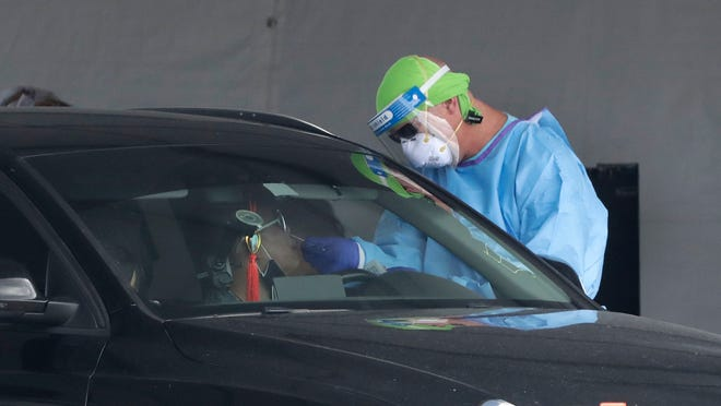 A healthcare worker takes a swab sample from a driver at a drive-through COVID-19 testing site outside Hard Rock Stadium, Wednesday, July 8, 2020, in Miami Gardens, Fla. Florida is one of the nation's hot spots for coronavirus.