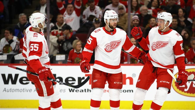 Red Wings defenseman Niklas Kronwall, left, and forward Anthony Mantha greet Mike Green after his first-period goal Sunday in Chicago.