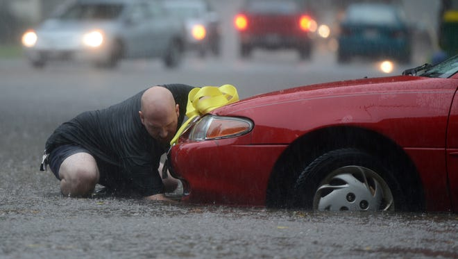 A PuroClean employee tries to hook up a cable to tow a car out of high water at the intersection of Hubbard Street and Woodlawn Avenue on Green Bay's west side on Tuesday morning.