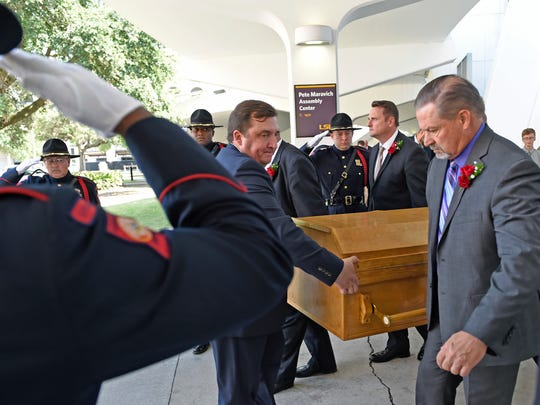 The casket is brought to the hearse after the funeral