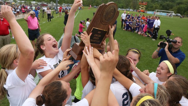 Members of the Sioux City Bishop Heelan girls soccer team celebrate after beating Nevada, 2-0, in the Iowa Class 1A state soccer championship match at Cownie Sports Complex in Des Moines on Saturday, June 13, 2015.