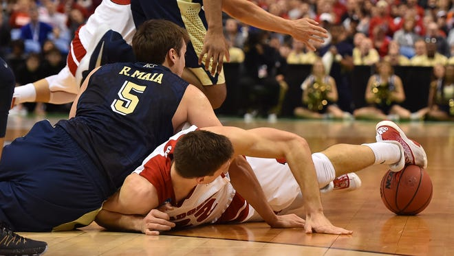 Wisconsin Badgers forward Ethan Happ (22) tries to retain control of the ball on the floor as Pittsburgh Panthers forward Rafael Maia (5) looks on during the first half of their 47-43 win on Friday.