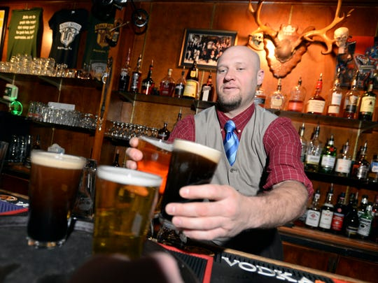 Lee Slack gets a round of beers out to a waiter while working behind the bar at Noble Savage.