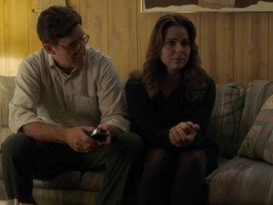 Karen and Ted Wheeler (played by Joe Chrest) sit on a couch in a scene from Stranger Things.