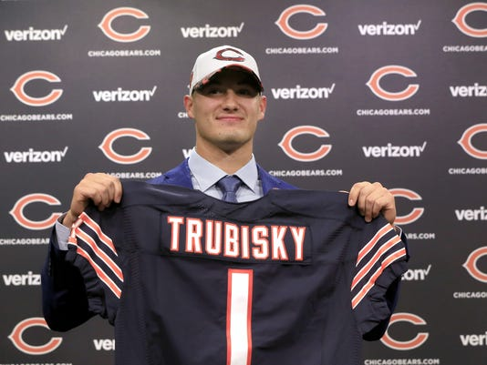 FILE - In this April 28, 2017, file photo, quarterback Mitchell Trubisky, the Chicago Bears' No. 1 pick in the first round of the NFL football draft pick, poses with a Bears' jersey during a news conference in Lake Forest, Ill. Passed on in the draft by his hometown Browns, Trubisky will line up against them when the Bears host winless Cleveland on Sunday. (AP Photo/Charles Rex Arbogast, File)