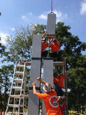 Members of Cincinnati Ironworkers Union 44 in August 2013 place the last of six segments representing the Twin Towers destroyed in the Sept. 11 attacks. Work has continued on the base in a pentagon shape which will be unveiled at a Sept. 11 ceremony.