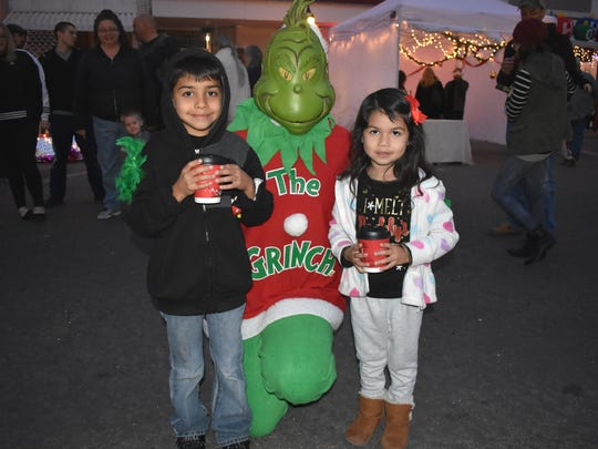 Dominic and Angelique Gonzales take a photo with the Grinch during Olde Fashioned Christmas Saturday.