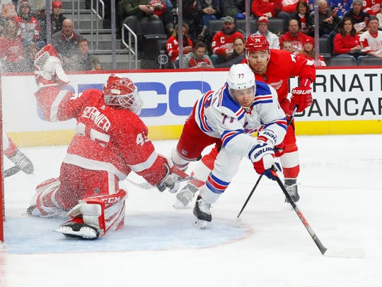 Detroit Red Wings goaltender Jonathan Bernier (45) stops a shot by New York Rangers' Tony DeAngelo (77) as Madison Bowey (74) defends during the third period of an NHL hockey game Saturday, Feb. 1, 2020, in Detroit. (AP Photo/Paul Sancya)