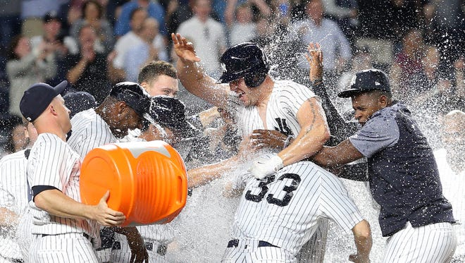 The Yankees' Matt Holliday is bombarded by teammates after his game-winning three-run home run against the Orioles at Yankee Stadium in New York.