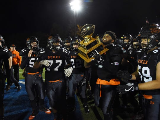 Marlboro's football team carries the trophy off the field after winning the Class B final against New Paltz at Middletown High School.