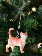 A plastic cat toy turned into a Christmas tree ornament with a bit of Sugru, a dough-like substance that hardens into silicone rubber, used to attach a split ring for hanging.