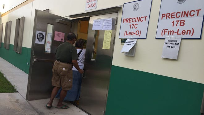 Voters enter a polling site at John F. Kennedy High School in Tamuning.