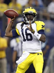 Michigan Wolverines quarterback Denard Robinson throws