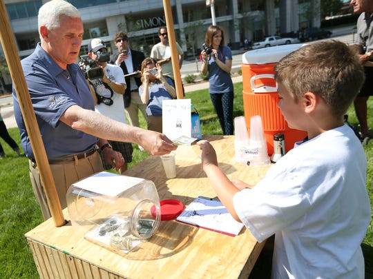 Gov. Mike Pence bought a glass of lemonade from Nathan Walsh (right), 7, who was working a lemonade stand at the Statehouse on last year's Lemonade Day.