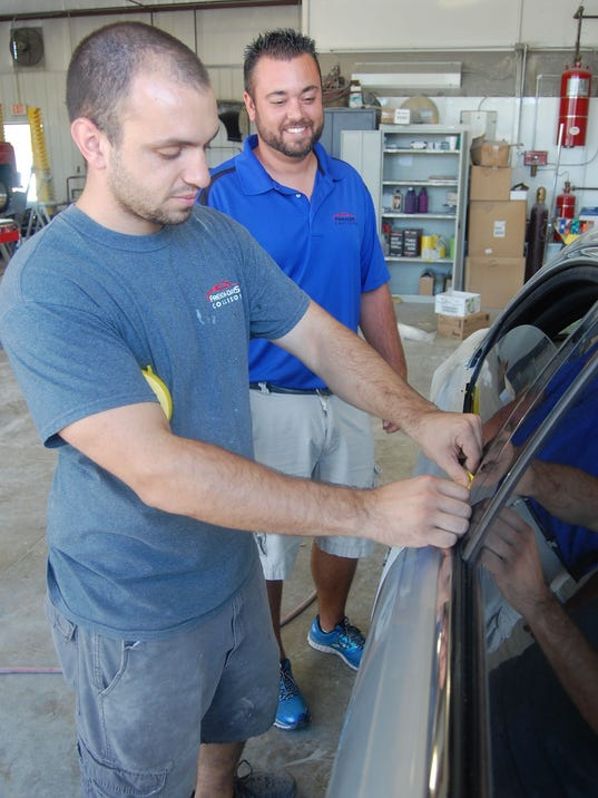 Brandon Davis (right) watches Jesse Webb prepare a car for painting.jpg