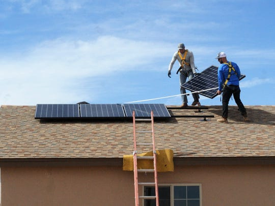 Installers position solar panels on a new home. Kentucky is changing how utilities can credit solar power that is added back into the power grid.