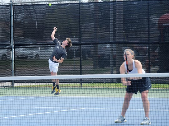 Abilene High's Max Owen serves behind partner Katherine
