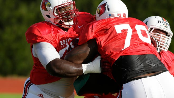 East lineman John Miller, of Louisville, left, blocks Jamon Brown, of Louisville,  during practice for the East-West Shrine college football game Tuesday, Jan. 13, 2015, in St. Petersburg, Fla. (AP Photo/Chris O'Meara)