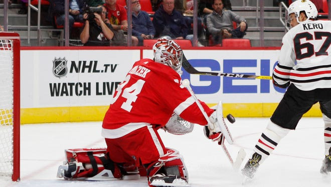 Detroit Red Wings goalie Petr Mrazek (34) makes a save against Chicago Blackhawks center Tanner Kero (67) during the first period at Little Caesars Arena.