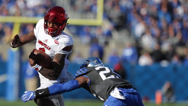 Louisville's Lamar Jackson avoided a Kentucky tackler on his way to a long gain. Nov. 24, 2017.