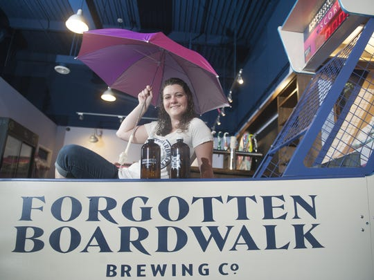 Jamie Queli, owner of Forgotten Boardwalk Brewing Co. in Cherry Hill, sits by a  Skee-Ball machine in her brewery's tasting room in this 2014 photo.