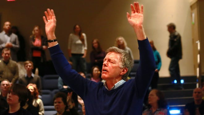 Rev. Ken Wilson of the Vineyard Church of Ann Arbor lifts his hands in praise during  service on March 23, 2014.