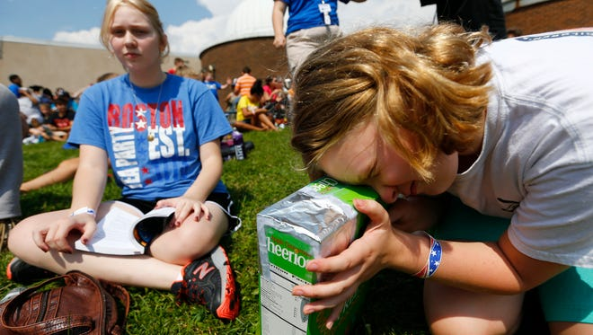From left, Danielle and Delanie Curry of Endwell view the solar eclipse through a camera obscura they created out of a cereal box at the Kopernik Observatory & Science Center in Vestal on Monday August 21, 2017.