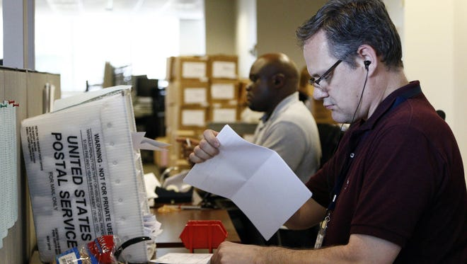 David Snow, an auditor with the Mississippi Department of Revenue, sorts a stack of tax returns in early May along with other auditors, revenue officers, and customer service agents.