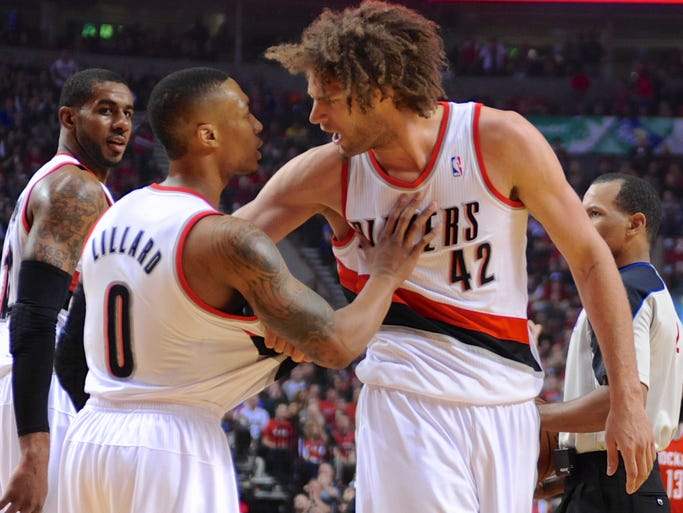 Portland Trail Blazers' Damian Lillard (0) speaks to Robin Lopez (42) after Lopez was called for a foul against the Houston Rockets during the first half of game four of an NBA basketball first-round playoff series game in Portland, Ore., Sunday March 30, 2014. (AP Photo/Greg Wahl-Stephens)