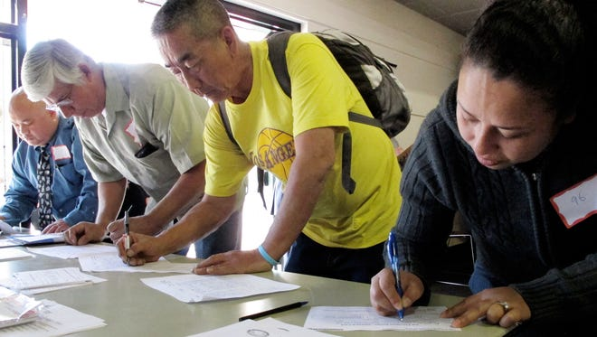 Job candidates fill out forms for employment interviews at a job fair in Bell, Calif., in March 2012.